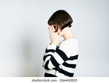 beautiful young sad woman hides face, short haircut, studio photo on background