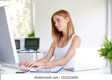 Beautiful young sales assistant businesswoman typing on computer's keyboard at office desk.
