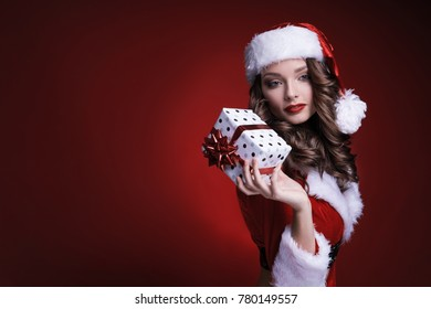 Beautiful young Santa girl with gift on red background. Brunette model holding box with ribbon in hand.