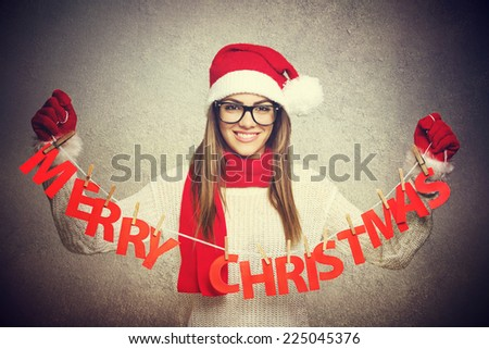 8700d6698b166 Beautiful young Santa woman with Merry Christmas decoration. Young teenage  girl with glasses with knitted