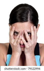 A beautiful young scared or surprised woman looking through her hands