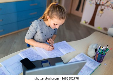 Beautiful young school girl working at home in her room with a laptop and class notes studying in a virtual class. Distance education and e-learning, online learning concept during quarantine