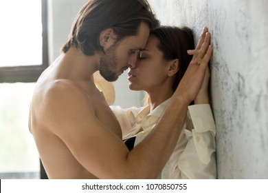 Beautiful young sensual couple holding hands leaning on wall, loving millennial affectionate  man and woman getting closer to kiss each other teasing enjoying tenderness and intimacy, feeling desire