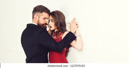 Beautiful young sensual couple holding hands leaning on wall, loving brutal bearded man and affectionate woman getting closer to kiss each other teasing enjoying tenderness and intimacy feeling desire