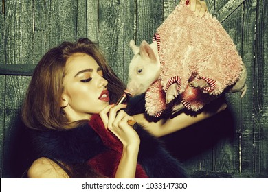 Beautiful young sensual fashionable woman in stylish scarf holding cute pink small pig pet in cloth and lipstick in hands on wooden background, horizontal picture