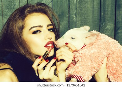 Beautiful young sensual fashionable woman holding cute pink small pig pet in cloth and lipstick in hands on wooden background, horizontal picture