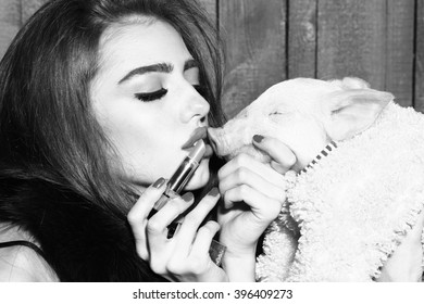 Beautiful young sensual fashionable woman holding cute pink small pig pet in cloth and lipstick in hands on wooden background black and white, horizontal picture