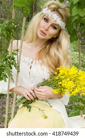 Beautiful Young sensual Woman BLONDE MODEL SITS In amazing dress on a swing suspended from the TREE in the forest, meadow  white flowers SPRING AND NATURE