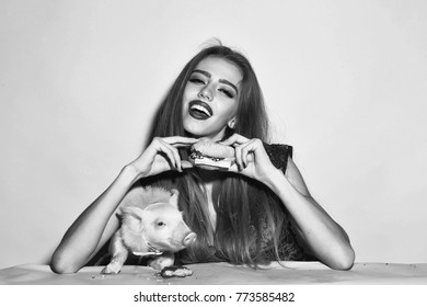 Beautiful young sensual woman and cute pink small pig pet in cloth eating tasty big fresh burger on yellow background, horizontal picture