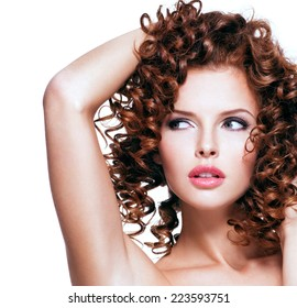Beautiful young sensual woman touching her hair by hands. Beautiful face with curly hairstyle, isolated on white.