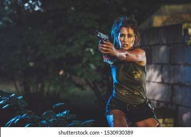 Beautiful young serious woman special forces holding gun and getting ready for the attack in abandoned ruin.