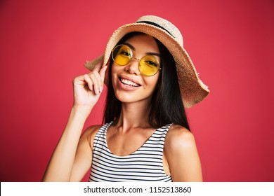 Beautiful young sexy asian woman in sunglasses and hat looks on camera. Girl over pink background is smiling