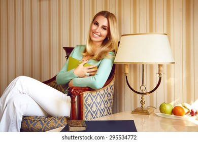 Beautiful young sexy blond girl with makeup woman dressed in a trendy, stylish clothing collection comfortable sitting in chair in room reading a good book, considering album, lamp, resting relaxing