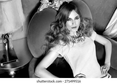 Beautiful young sexy blond woman with curly hair jewelry  makeup business woman reading a rest in a room  in the luxurious interior in stylish clothes collection dress