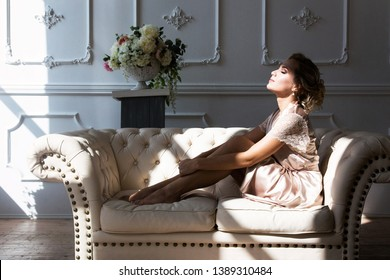 Beautiful young sexy blonde woman in a silk robe sitting on a couch hugging her legs in front of a window in the rays of incident light