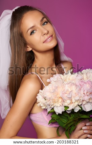 c9c4d943dfe Beautiful young sexy bride in white veil and pale pink lace lingerie with  bouquet of peonies