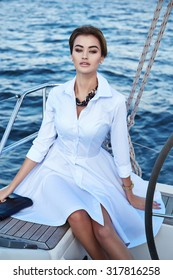 Beautiful young sexy brunette girl in a dress and makeup, summer trip on a yacht with white sails on the sea or ocean in the Gulf marine of the wind and the breeze in the sun tans romantic