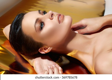 Beautiful young sexy brunette girl portrait lying on the shining gold background, makeup evening party, long lush lashes, plump parted lips, cosmetics, body care, shoulders neck soft skin, bronze tan