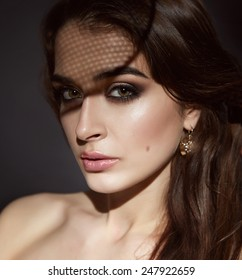 Beautiful young sexy brunette woman with bright evening make-up perfect smooth skin cosmetics cream face care, jewelry, beauty salon, magazine, close-up portrait