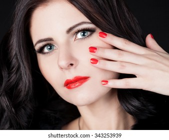 Beautiful young sexy elegant woman face, has happy fun blue eyes with contact lenses, brunette nature hair, hand with nail polish manicure, red lips. Pure makeup. Black background.