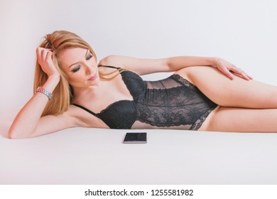 Beautiful young sexy erotic woman in black lace negligee lying on bed, waiting for phone call
