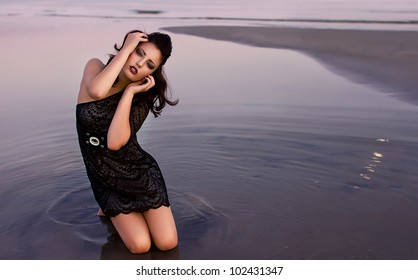 Beautiful young sexy fashion model in dress in  the sea