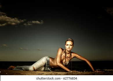 Beautiful young sexy fashion model in jeans by the sea in Greece