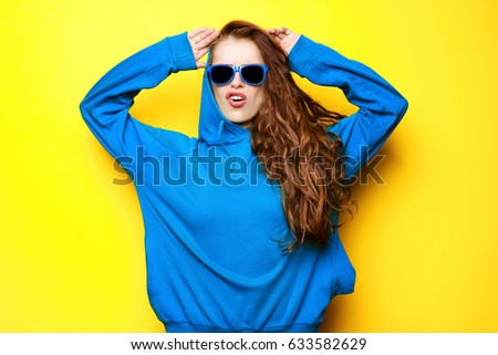 5bc82bd87f Beautiful young sexy girl in blue blouse and sunglasses having fun and  laughing on a yellow