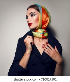 Beautiful young sexy girl with bright make-up in a bright headscarf.