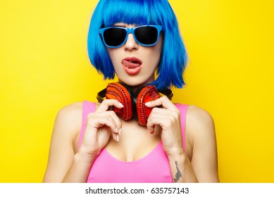 Beautiful young sexy girl dj in blue wig blue sunglasses and pink bathing suit having fun and listening to music in red headphones on yellow background