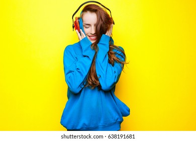 Beautiful young sexy girl DJ in a blue jacket listening music in red headphones on a yellow background and having fun