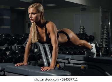 Beautiful young sexy girl doing exercises in fitness club on the benches