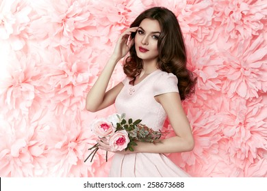 Beautiful young sexy girl with long wavy brunette hair with a bright evening make-up perfect summer tan thin figure dressed in colored short dress holding flower pink