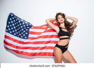 Beautiful young sexy girl posing in bikini with american flag isolated on the white background