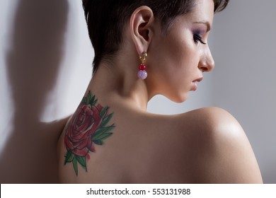 Beautiful young sexy girl with short hair with tattoo on his back is against the wall with bare shoulders sad