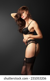 The beautiful young sexy girl in stockings poses in studio on black background.