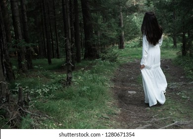beautiful young sexy girl walks and rests in a fairy forest, she has a white gentle dress and a tiara in her hair, she looks like an unearthly nymph, light and graceful, trees are juicy mint-colored