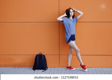 Beautiful young sexy hipster girl standing near urban orange wall in blue shirt, denim shorts, sneakers with her pink backpack standing on the ground, a lot of copyspace.