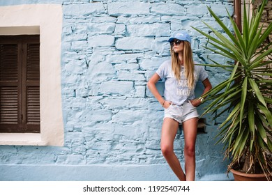 Beautiful young sexy hipster girl posing and smiling near urban blue wall background in yellow dress, shorts, shirt, sneakers, sunglasses.