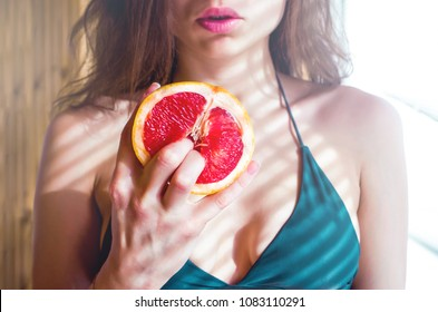beautiful young sexy woman in bikini holding two fingers on grapefruit  on the background of her lips and  breast. Sex concept.