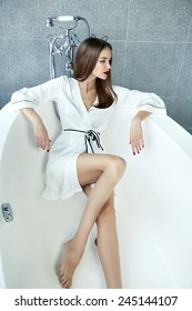 Beautiful young sexy woman with dark hair, evening make-up, red lips and manicure sitting in the bathroom in a white silk robe, holding a red rose smiling white teeth, Valentine's Day
