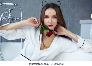 Beautiful young sexy woman with dark hair, evening make-up, red lips and manicure sitting in the bathroom in a white silk robe, holding a red rose smiling white teeth, Valentine