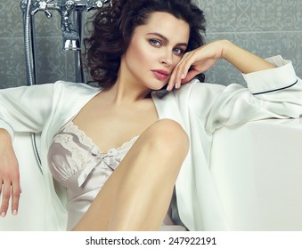 Beautiful young sexy woman with dark hair, evening make-up, red lips and manicure sitting in the bathroom in a white silk robe, Valentine