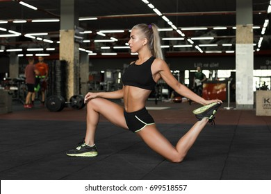 Beautiful young sexy woman do sport exercises in sexy uniform. The girl is looking  Blond sexy girl in gym.