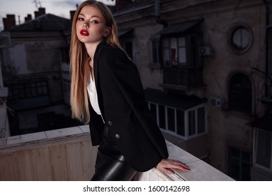 Beautiful young sexy woman, glamour girl in the black elegant jacket, suit, makeup red lipstick on the office balcony with the urban background. night old city