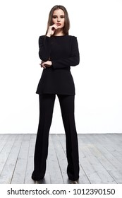 Beautiful young sexy woman with long brunette hair with bright evening make up perfect summer tan thin figure wear black suit jacket pants high heels shoes perfect body shape accessory businesswoman.