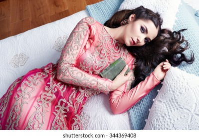 Beautiful young sexy woman with long dark hair brunette and decoration in evening dress of silk lace, room bedroom in Moroccan style velvet pillows luxurious furniture fashion harem concubine bed