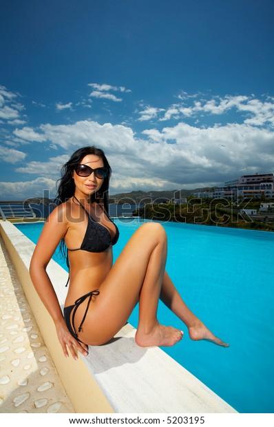 Beautiful young Sexy woman sitting in bikini next to swimming pool