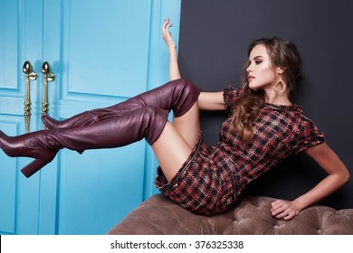 Beautiful young sexy woman in smart evening dress red silk dress new stylish fashion collection autumn winter season, long brown hair, shoes, interior blue door in the bedroom room
