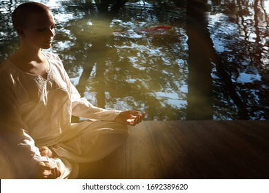 Beautiful young shaved bald girl meditates on the background of reflection in the water with a floating red carp..